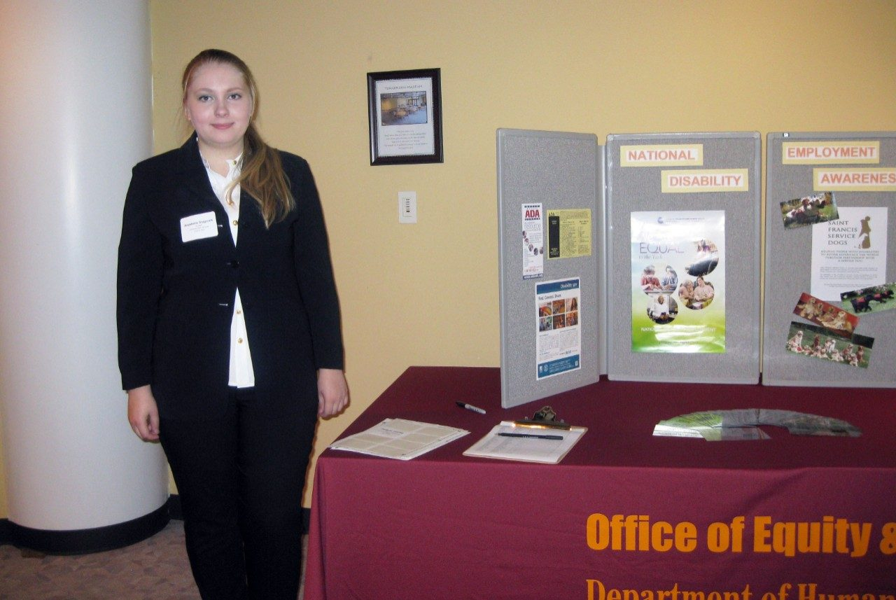 NDEAM display: Ana Grygorets, Americans with Disabilities Act student worker, stands next to the National Disability Employment Awareness Month display.