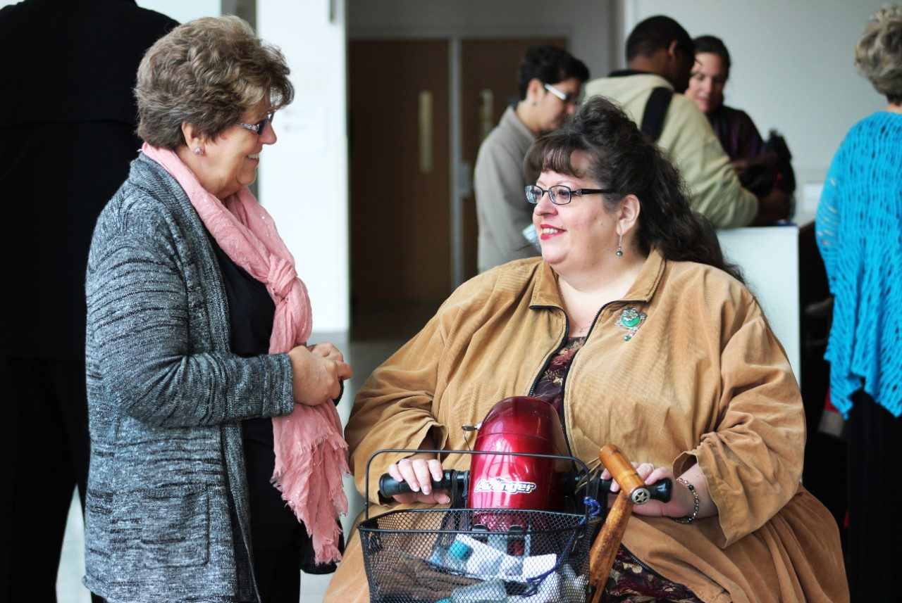 Sandra Ratliff, administrative assistant for University ADA Services, speaks with a participant after the presentation