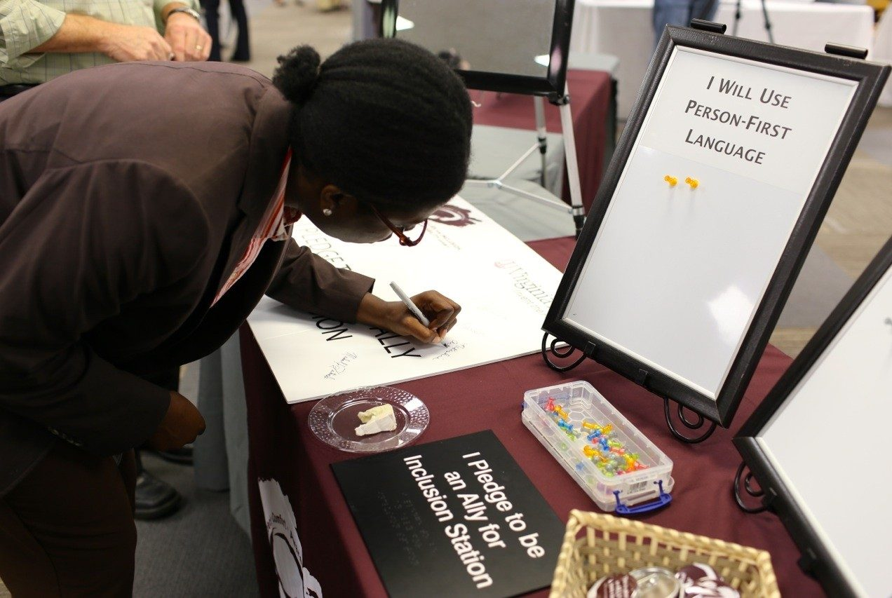 "An employee signs the ""I pledge to be an inclusion ally"" poster."