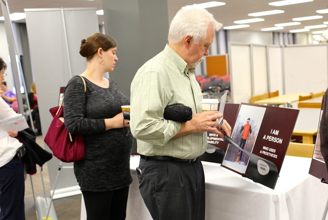 Employees browsing the Ability Exhibit stations.